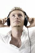 foto of partially clothed  - A caucasian man listening to headphones music with a white background - JPG