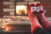 Feet In Woollen Red Christmas Socks By The Fireplace. Close Up On Feet. Tabletop For Display Your Ch poster