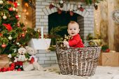 Portrait Of Playful Happy Cute Little Baby Boy, Who Sits In The Basket In A Decorated Room At Home. poster