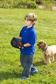stock photo of young boy  - Young boy playing catch with dog outside on a summer day - JPG