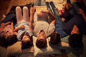 Overhead View Of Family Enjoying Movie Night At Home Together poster