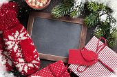 Christmas fir tree, gift, mittens and chalkboard for your greetings. Top view with copyspace poster