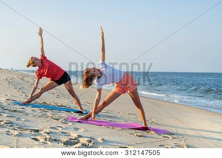poster of Young Women Practicing Yoga On The Beach. Beautiful Girls Doing Yoga Standing In Warrior Pose At You