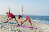 Young Women Practicing Yoga On The Beach. Beautiful Girls Doing Yoga Standing In Warrior Pose At You poster