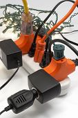 image of christmas lights  - overloaded electrical power strip with christmas lights in background - JPG