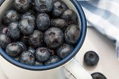 Close-up Of Fresh Blueberries In White Porcelain Cup. Background With Blue Tones Space To Insert Tex poster