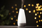 Modern Aroma Humidifier On Wooden Table Against Blurred Lights, Space For Text poster