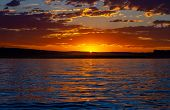 Last Light Of Day Over Wahweap Bay In Lake Powell, Arizona.  The Sun Is Sinking Behind The Distant M poster