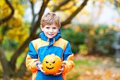 Happy Cute Little Kid Boy With Halloween Pumpkin Lantern. Funny Child In Colorful Clothes Having Fun poster