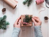 Christmas Gift Wrapping Background.female Hands Holding Christmas Present Box Wrapped In Kraft, Top  poster