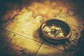 Vintage Adventure Concept. Antique Compass On The Aged World Map. Closeup Photo. Expedition Journey. poster