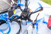 A Fpv High-speed Racing Drone Copter And Tools Lying On The Table poster
