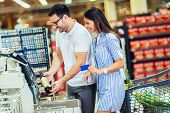 Couple With Bank Card Buying Food At Grocery Store Or Supermarket Self-checkout poster