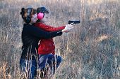 stock photo of protective eyewear  - Mother teaching her young daughter how to safely and correctly use a handgun - JPG