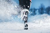 stock photo of cold-weather  - Athlete woman is running during winter training outside in cold snow weather.