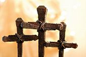 Easter images of rusty nail crosses with gold fabric and defocused lights as background.  Macro with