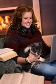 Smiling teenage girl sitting at fireplace at home learning with laptop and books. Happy brainy preoc