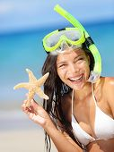 stock photo of watersports  - Summer beach vacation holidays woman wearing snorkeling mask showing star happy joyful and laughing - JPG