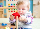 stock photo of playgroup  - cute little girl in the classroom early development plays with bright toys - JPG