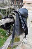 picture of girth  - Old Saddle Hanging on Rustic Wood Pole Fence - JPG