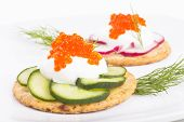 foto of banquette  - Red caviar on white chees and green cucumber appetiser on white background - JPG