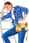 Young DIY handy woman with a problem standing on her stepladder with her head on her hand staring th