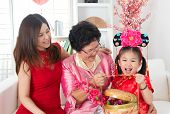 Beautiful grandchild visiting grandparent with gift during Chinese new year festival.