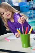 Cute little girl picking sketch pen from case at desk in classroom