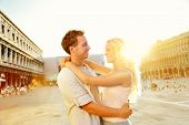 Love - romantic couple in Venice on Piazza San Marco. Young couple on travel vacation holidays huggi