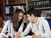 Portrait of teenage girl holding boy's hand while sitting at table in library