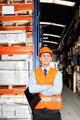 Confident young male supervisor in orange protective vest with arms crossed at warehouse