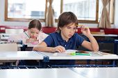 Thoughtful boy sitting at desk with classmate studying in background