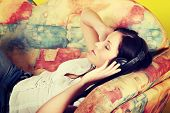 Young woman at home lying on sofa and listening music