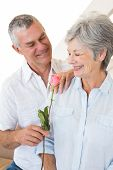 Senior man offering a rose to his partner at home in living room
