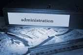 The word administration on blue business binder on a desk
