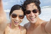 Man & woman Asian couple, boyfriend girlfriend in bikini, taking vacation selfie photograph at the b