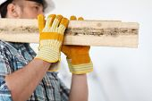 repair, building and home concept - close up of male in gloves and helmet carrying wooden boards on