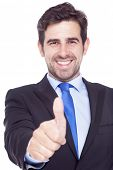 Smiling handsome businessman gesturing thumb up, isolated on a white background
