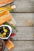 Italian food appetizer of olives, bread, olive oil and balsamic vinegar on wooden table background