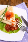 Pancake with salmon, red caviar and mayo, green onion, on plate, on color napkin, on wooden backgrou