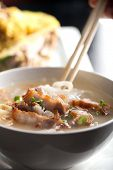 foto of crispy rice  - Closeup of a person eating Thai style crispy pork rice noodle soup from a bowl with chopsticks - JPG
