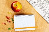 Red apple notepad and keyboard on wooden table