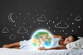 Cute girl sleeping in bed and looking at Earth planet. Elements of this image are furnished by NASA