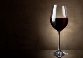 stock photo of canvas  - Dry red wine in wineglass on a canvas - JPG