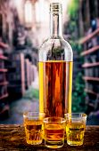 picture of spirit  - Bottle and three glass shots with yellow liqour resembling whiskey - JPG