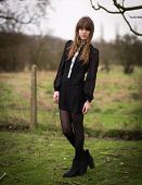 image of nylons  - Portrait of a beautiful young woman wearing a black dress nylons and boots standing in a country farm field hair blowing in the wind.