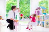 stock photo of doll  - Happy family young father and his little daughter cute curly toddler girl wearing a dress playing together with doll house having toy tea party in a white sunny nursery - JPG