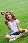 stock photo of  preteen girls  - Portrait of a preteen girl trowing apple in the air and with a pear in her other hand and green grass in the background - JPG
