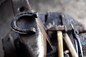 foto of anvil  - Color shot with a hammer a horse shoe and an anvil.