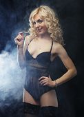 image of stripping women window  - young sexy blond woman in  lingerie over dark background - JPG